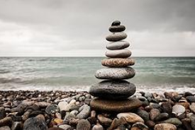 stones placed on top of each other on the beach, symbolizing the meaning of body mind spirit connection for Christine Ghali, doula
