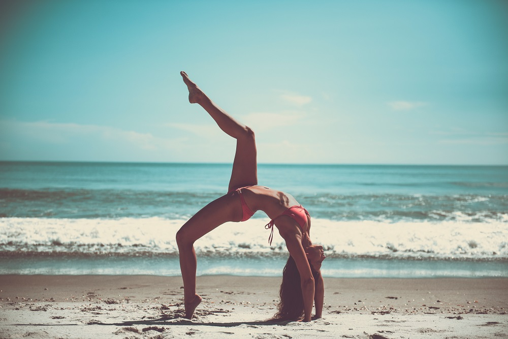 woman doing yoga on the beach, symbolizing the power of structural realignment