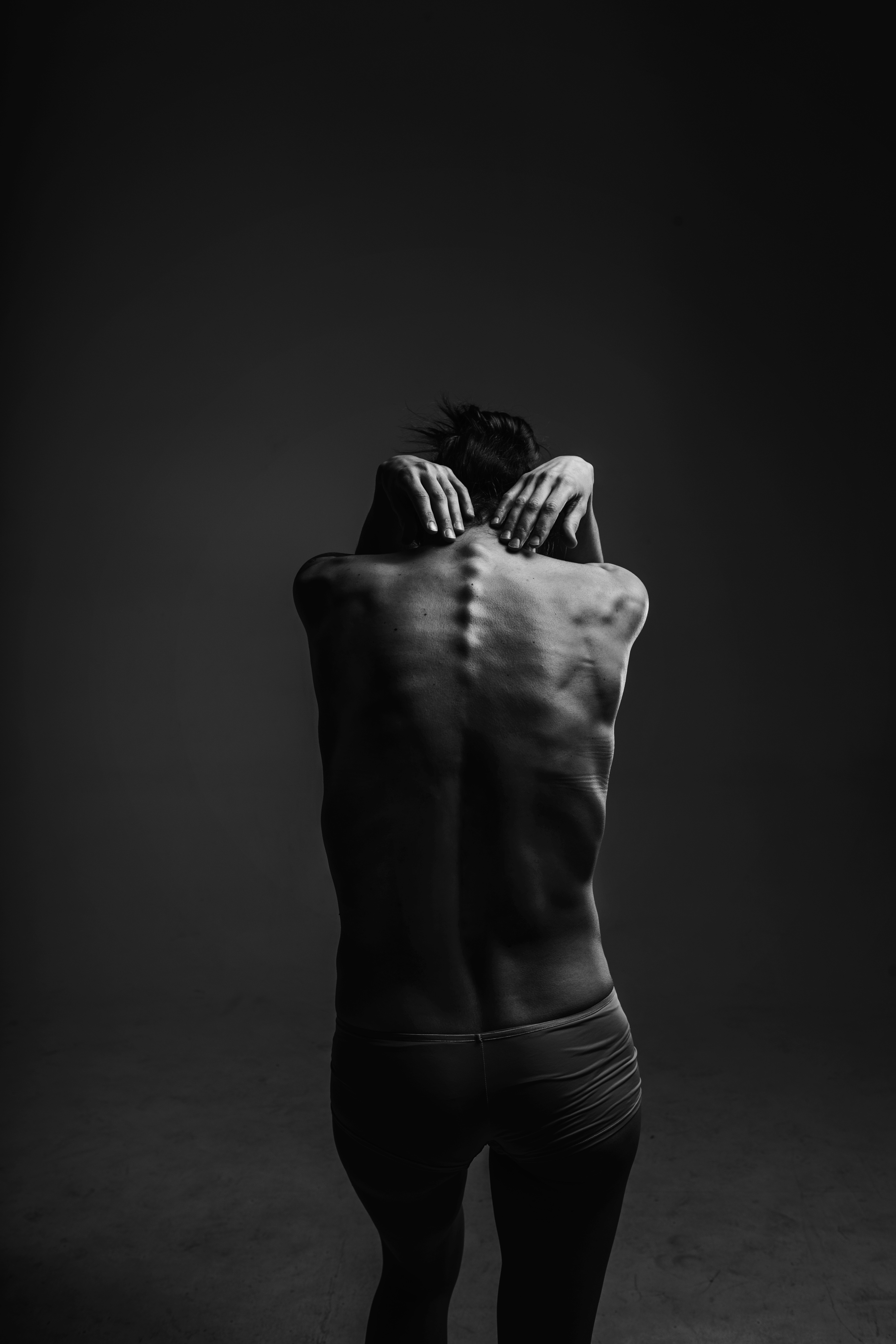 woman with back to camera, showing her spine and symbolizing the power of structural realignment