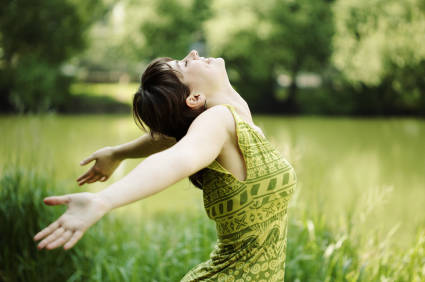 woman in green dress opening up her arms while being outside, symbolizing the power of a master cleanse experience
