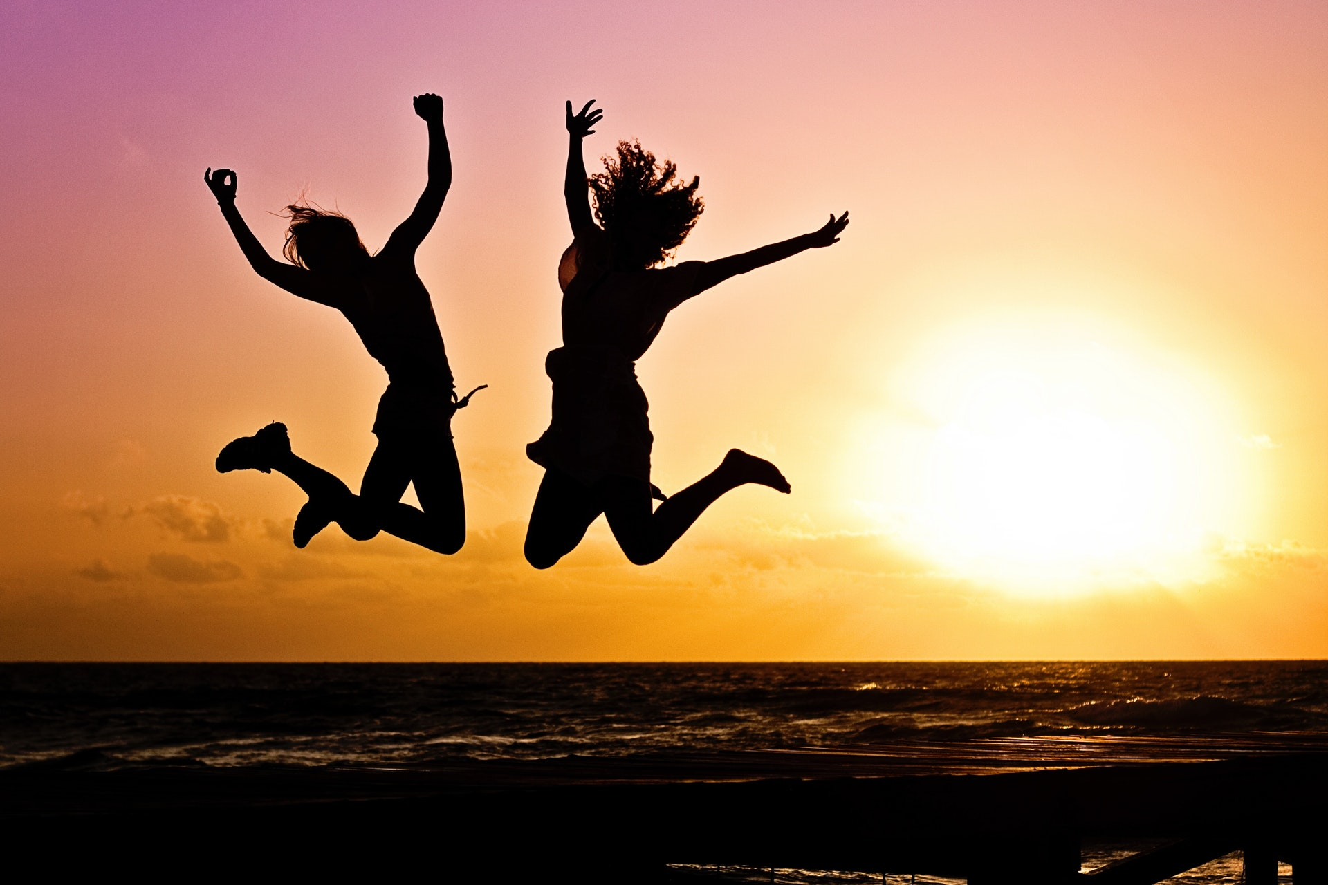 two people jumping up in the air, ocean behind them, after they did their master cleanse