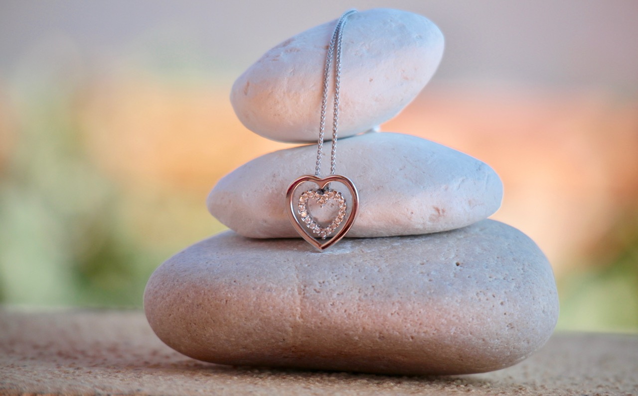 three river stones on top of each other and a silver necklace hanging down from the top stone with a diamant heart at the end, symbolizing the beauty of doing a master cleanse for mind, body and spirit