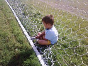 a boy fixing a soccer net, symbolizing the results of loving parenting