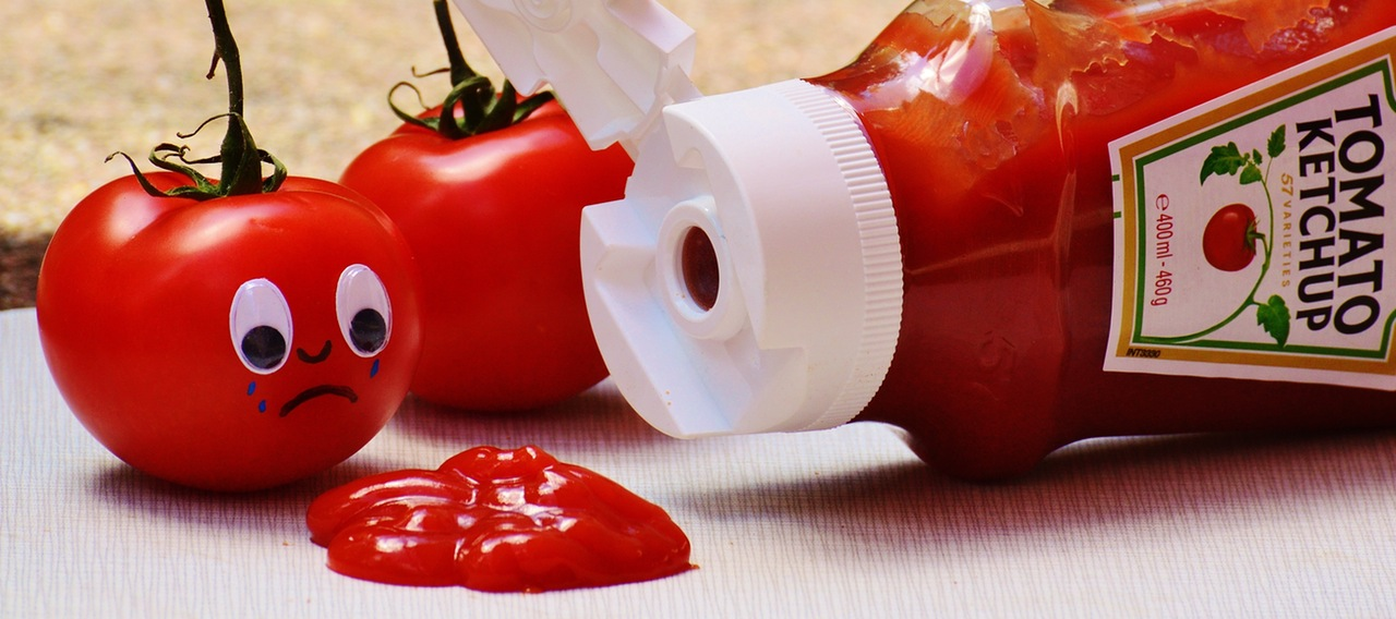 ketchup bottle with two tomatoes in front of it, tomatoes have sad faces about the dropping ketchup coming out of the bottle