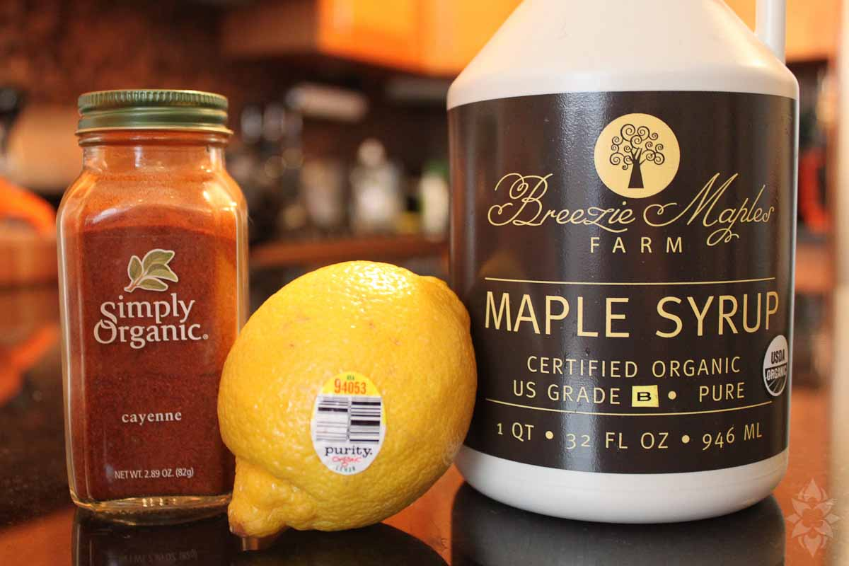 a bottle with simply organic cayenne pepper, an organic lemon, breezie maples farm maple syrup, important ingredients of a master cleanse