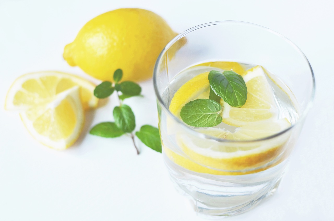 water glass with cutted pieces of organic lemon, part of Heather's master cleanse