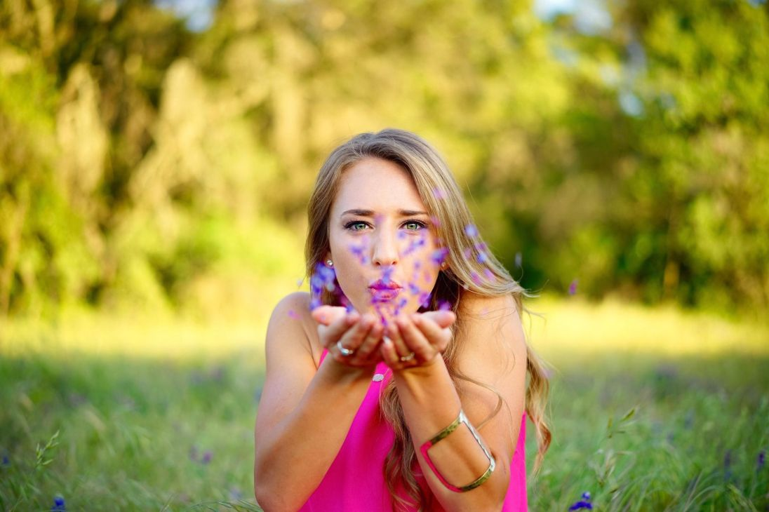 woman in pink dress and with blonde hair, blowing purple flower pedals off her hands, symbolizing the power of loving yourself quotes