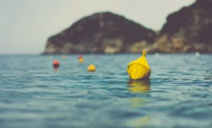 buoys swimming in the ocean in front of a cliff, 10 Buckets for Work Life Balance: #8 Increase Your Work Performance by Building Better Relationships at Work and with Others