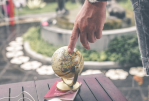 man in garden, next to table, using a small globe on top of his passport, finding joy in living in the moment