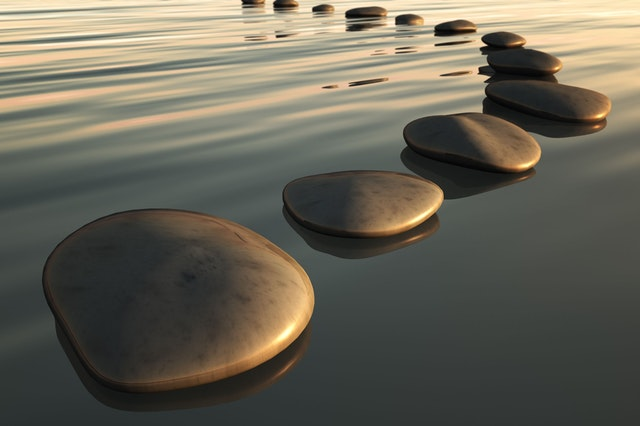 stepping stones placed in a lake, finding joy in being in nature