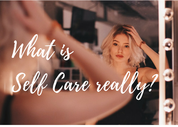 young woman with short blonde hair, looking in the mirror, asking herself what self care really is