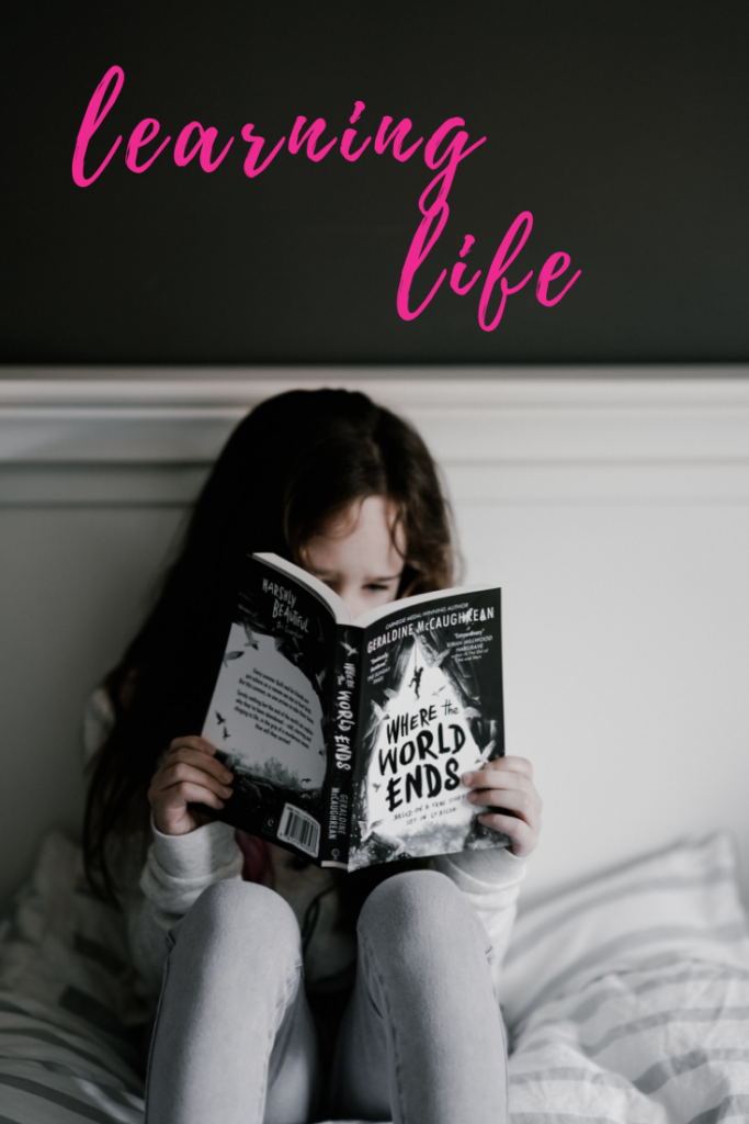a girl with long brown curly hair is reading a book, sitting on her bed, learning life, How Abuse Creates Abandonment that Leads to Loss of Trust