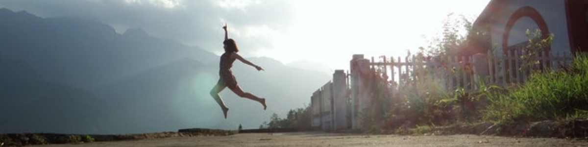woman with short hair and shorts is walking close to a village and jumping in the air, Living Pain Free: How to Move and Release Emotions