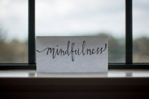 piece of paper with word mindfulness written on it in a window frame, overlooking the dunes, take care of yourself first