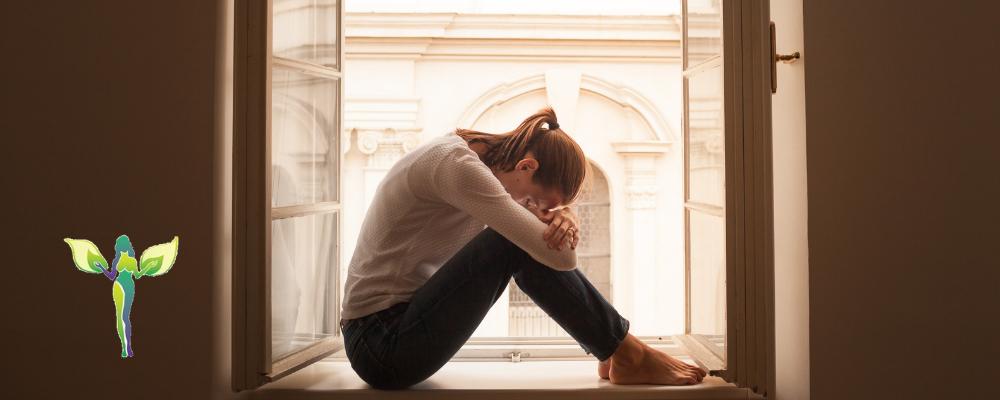 sad woman sitting in the windowseal