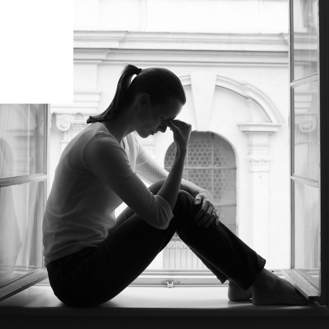 black and white image, woman with ponytail, white shirt and jeans, sitting in an open window frame, I support you