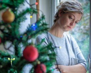 a blonde woman, looking sad and leaning against a window, in front of the Christmas tree, Be Yourself to Experience Joy and Happiness