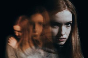 woman with long red hair and white face, looking scared and fearful, mental illness